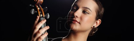 Photo for Attractive professional musician looking at violin isolated on black, horizontal crop - Royalty Free Image