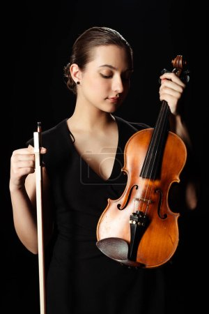 Photo for Beautiful professional musician holding violin isolated on black - Royalty Free Image