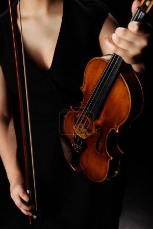 Photo pour Vue recadrée d'une musicienne tenant un violon sur scène sombre - image libre de droit