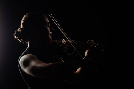 Photo for Silhouette of female musician playing on violin on dark stage - Royalty Free Image