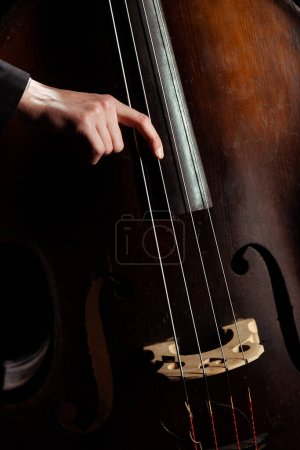 Photo for Cropped view of professional musician playing on double bass on dark stage - Royalty Free Image