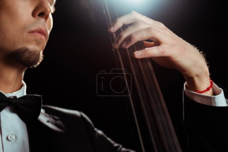 Photo for Cropped view of musician playing on contrabass on dark stage with back light - Royalty Free Image