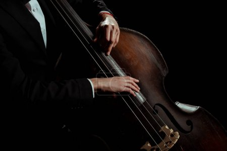 Photo for Cropped view of male professional musician playing on contrabass isolated on black - Royalty Free Image