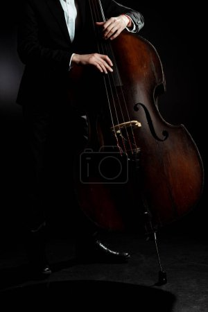 cropped view of professional musician playing on double bass on dark stage