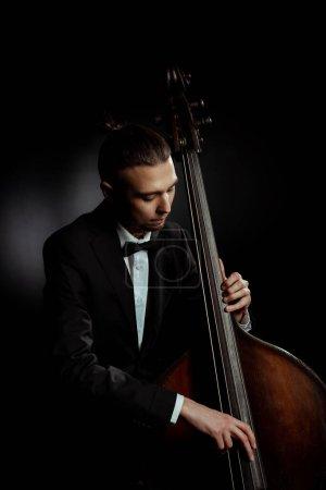 Profi-Musiker am Kontrabass auf dunkler Bühne