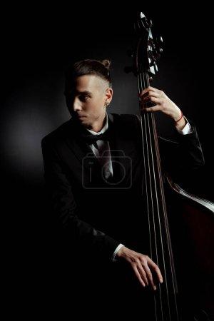 Photo pour Musicien professionnel jouant sur contrebasse sur scène sombre - image libre de droit