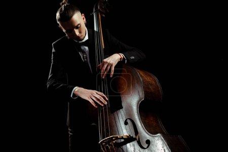 Photo pour Mâle musicien jouer sur contrebasse isolé sur noir - image libre de droit