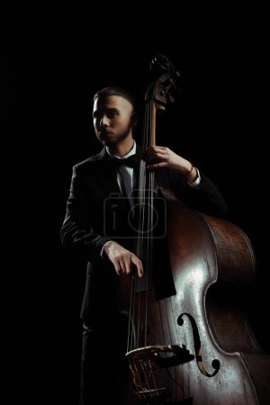 Photo for Professional musician playing on contrabass isolated on black - Royalty Free Image
