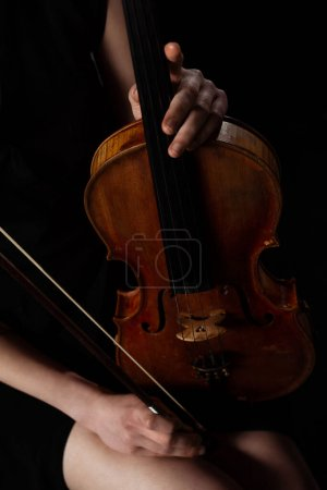 Photo for Cropped view of female musician holding violin on dark stage - Royalty Free Image