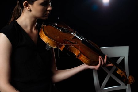 Photo pour Belle musicienne jouant sur violon noir avec contre-jour - image libre de droit