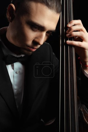 Photo for Professional handsome musician playing on contrabass isolated on black - Royalty Free Image