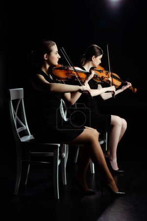 Photo for Professional young musicians playing classical music on violins on dark stage - Royalty Free Image