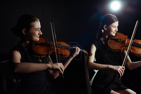 Photo for Happy attractive musicians playing on violins on dark stage with back light - Royalty Free Image