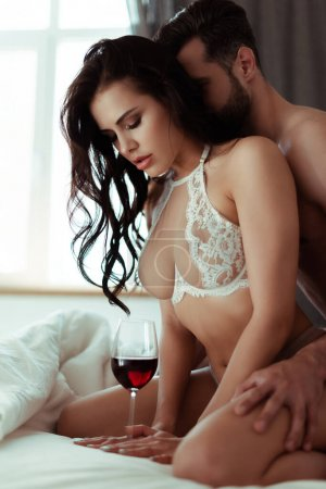sexy undressed couple with red wine in bed