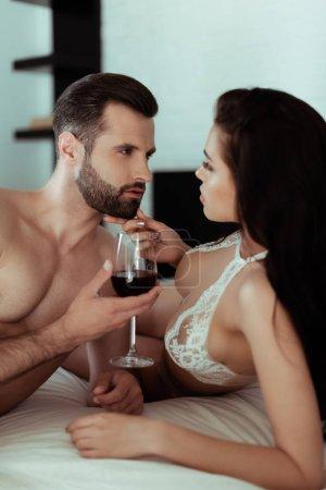 Photo pour Sexy couple déshabillé boire du vin rouge au lit - image libre de droit