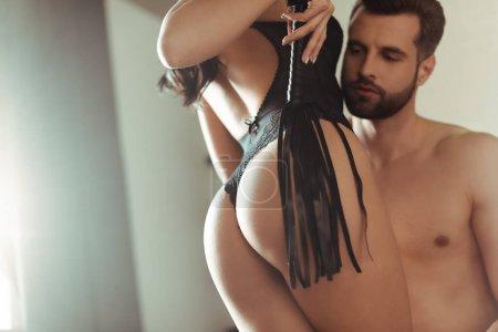Photo pour Vue recadrée de femme sexy avec fouet fouet près de l'homme - image libre de droit