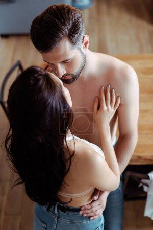 Photo pour Vue aérienne de sexy jeune couple déshabillé étreignant dans la cuisine - image libre de droit