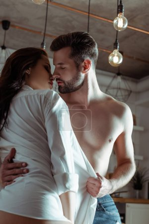 Photo for Sexy young passionate couple kissing in kitchen - Royalty Free Image