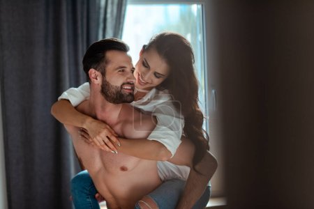 Photo for Selective focus of happy sexy young brunette woman in shirt hugging man with bare torso - Royalty Free Image
