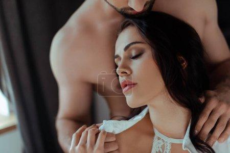 Photo pour Vue recadrée de sexy homme avec torse nu embrasser femme déshabillée au lit - image libre de droit