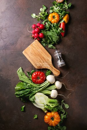 Photo for Variety of wet raw fresh organic colorful vegetables tomatoes, radish with leaves, fennel, paprika, salt, pepper, wooden chopping board for salad over dark brown texture background. Top view, space. - Royalty Free Image