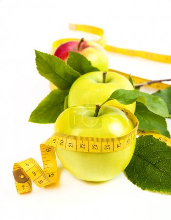 dieting. green, yellow apple with leaf and tape isolated on a wh