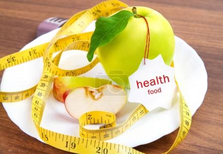 dieting and health food. Yellow, green apple with leaf, tape and