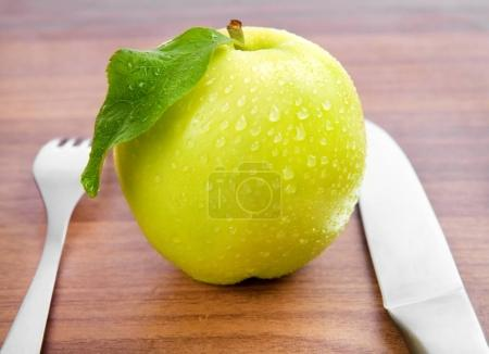 clean green apple with leaf on wooden table with fork and knife