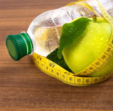 Apple core, bottled water for healthy life over a wooden backgro