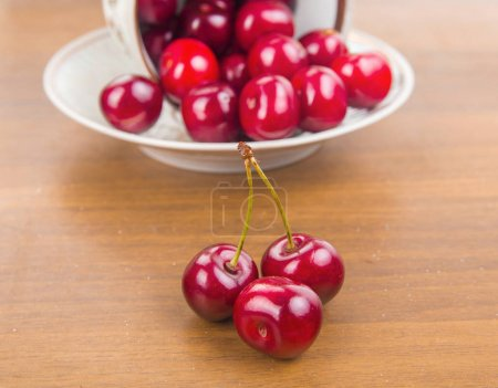 Sweet cherries in a white cup on a wooden table with two cherrie