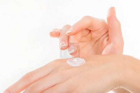 Beautiful young woman hands with cream, isolated on white