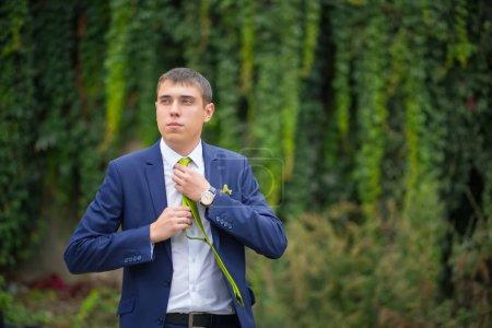 walking groom in park take tie