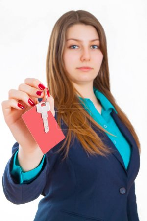 Attractive serious girl in a classic suit holding in her hand ke