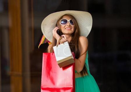 Photo pour Superbe et très belle femme en robe avec de longs cheveux bruns tenant téléphone portable et sacs à provisions colorés - image libre de droit