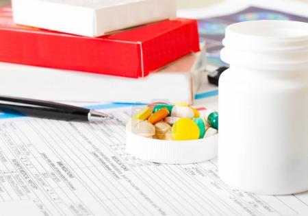 doctor workplace with pills and bottle on patient history database