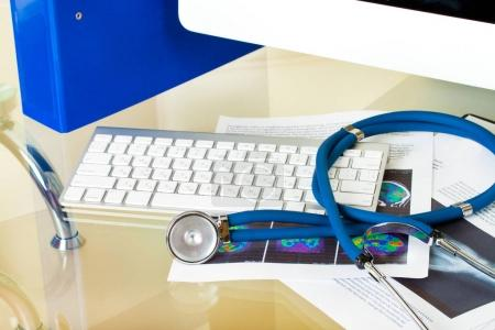 Doctor workplace with stethoscope on patient history database and x-ray with keyboard
