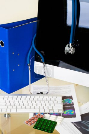 Doctor workplace with pills and keyboard with patient history database