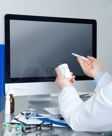 Photo for Male doctor holding bottle of pills and pen in hands in front of computer display - Royalty Free Image