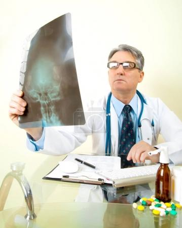 male doctor looking at a x-ray image in office