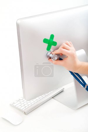 Photo for Hand putting hand with stethoscope on monitor backside, computer repair concept - Royalty Free Image