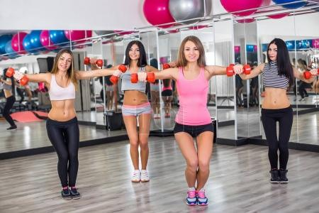Four Gorgeous brunette women lifting some weights and working on her biceps in a gym