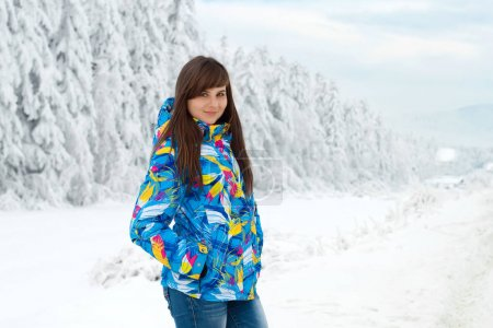 beautiful woman in colorful jacket in winter forest