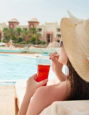 Woman in hat relaxing at the poolside with cosmopolitan cocktail