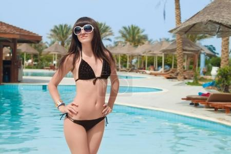 Shiny beautiful girl. Portrait of beautiful young women in bikini smiling on camera with a swimming pool on the background