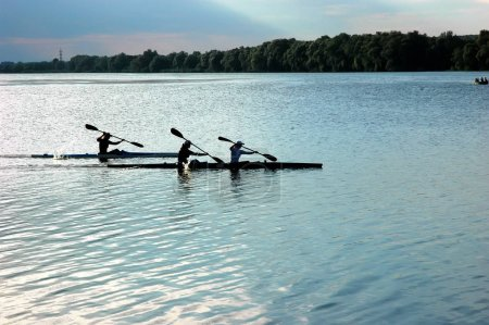 rowers paddling in a beautiful lake
