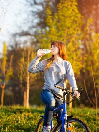 A young beautiful girl is drinking water from a bottle while sitting on a bicycle - Outdoors at sunset