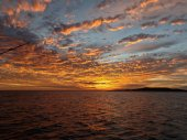 Vibrant Orange colored cloudy sunset seascape. Coastal Australia