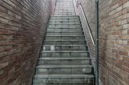 Old underground concrete stairs with brown brick walls