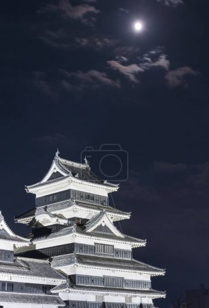 view of Matsumoto castle at nighttime with full moon