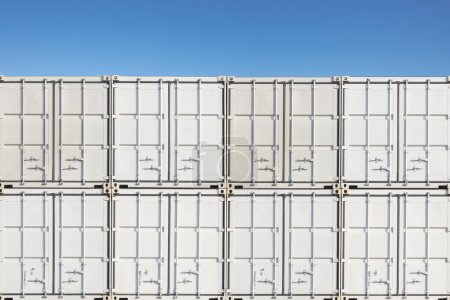 Stack of containers shipping at dockyard against blue sky